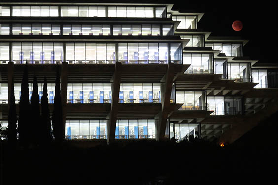 UC San Diego Geisel Library - empty but lit from within, against a night sky and full moon overhead