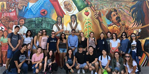 UC San Diego Communication 190 class poses for a group photo in front of mural at Chicano Park, San Diego, CA