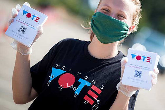 UC San Diego student wearing face mask hands out flyers with Tritons Vote logo
