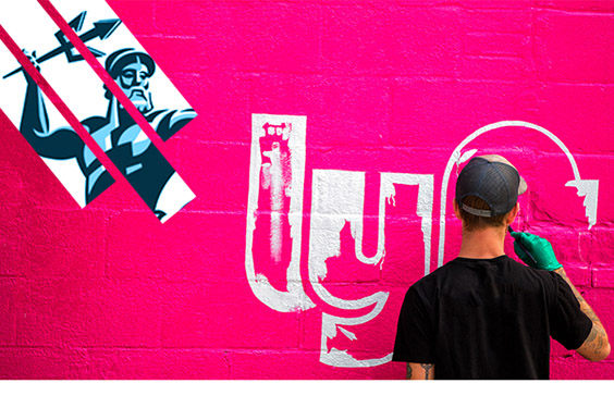 UC San Diego logo and Lyft logo - graffiti artist paints both logos onto a bright pink wall