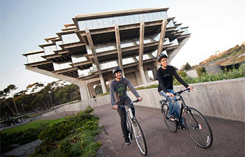 Two bicyclists riding on campus near Geisel Library